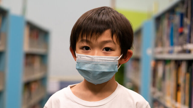 One cute Asian boy is wearing a disposal surgical mask at the public library. Kid and virus protection at the school.