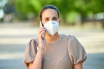 Woman with antiviral mask using mobile phone on the street