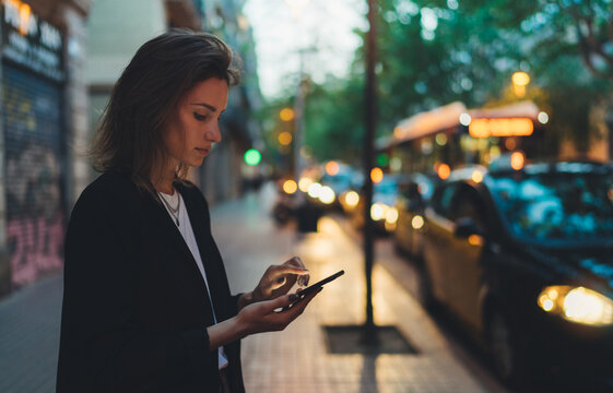 Traveler woman calling mobile phone waiting yellow taxi in evening street europe city Barcelona. Girl tourist using smartphone internet online gadget cellphone on background bokeh headlights of cars