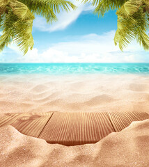 Wall Mural - Tropical fine sandy beach with blured sea sun sky clouds background with wooden table top and empty space for product advertisement Montage of summer relaxation background