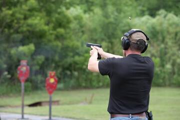 Man shooting with a gun at the outdoor range