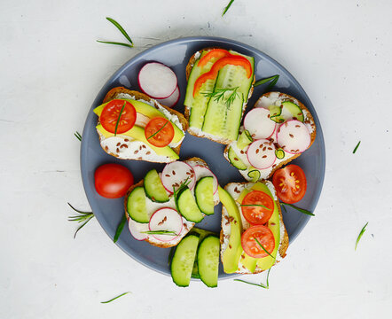 vegetarian sandwiches with cream cheese and vegetables: cucumber, radish, tomato, avocado, rosemary on a white background. Different kinds of colorful sandwiches. Fresh healthy concept food.Copy space