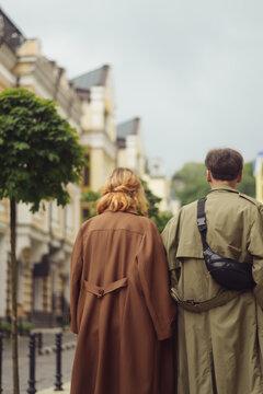 A couple in love walking down the street wearing vintage loose cloaks in Kiev