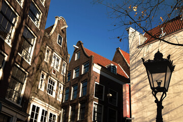 Fototapeta Glimpse of typical duch inclined houses in the center of Amsterdam, the most touristic city in the Netherlands. obraz