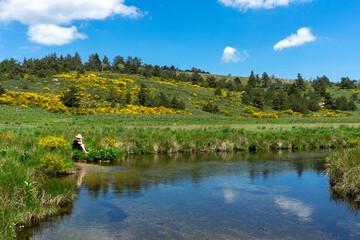 Une femme sur le bord d'une rivière en montagne