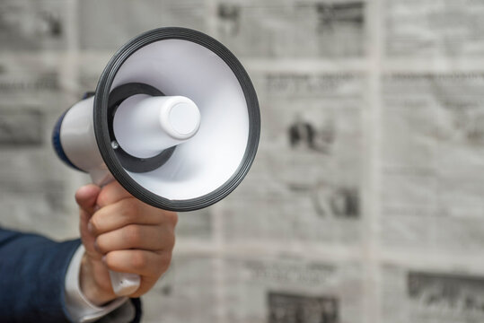 A man holding a megaphone on background of newspapers. News message concept