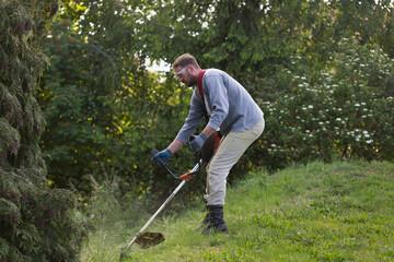Fototapeta Mężczyzna z ręczną kosiarką ścina trawę w ogrodzie obraz