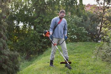 Fototapeta mężczyzna przycina w ogrodzie trawę kosiarką spalinową obraz