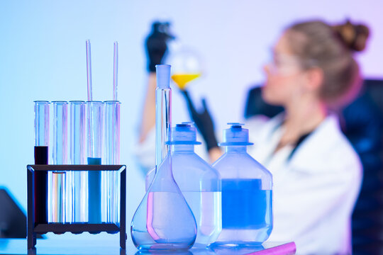 Table in a chemical laboratory on the background of a girl with a test tube in her hands. The girl is conducting a study of a yellow chemical liquid. Quality control of products.