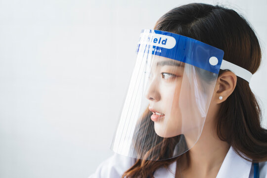 Medical healthcare beautiful Asian doctor wearing face shield mask protection from infectious disease virus bacteria germs coronavirus covid-19, safety protection working in hospital modern office