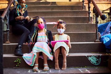 Young Mixed Race Girls Playing on Tablet Wearing Masks on Brownstone Stoop