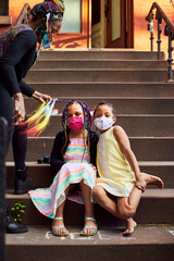 Young Mixed Race Girls Having Their Hair Braided Wearing Masks on Brownstone Stoop