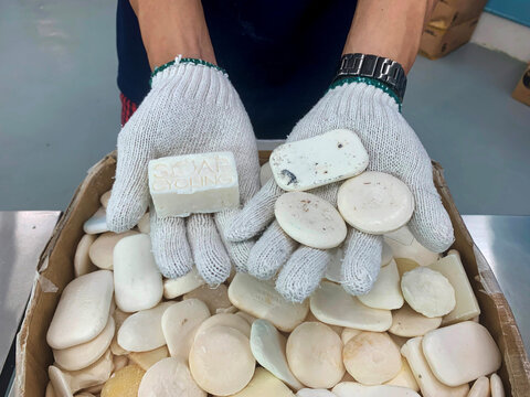 A staff member of Soap Cycling, a Hong Kong-based non-governmental organisation, shows used soap collected from hotels for recycling, and reprocessed soap, at their warehouse in Hong Kong
