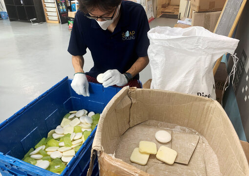 A staff member of Soap Cycling, a Hong Kong-based non-governmental organisation, sorts used soap collected from hotels before reprocessing them at their warehouse, in Hong Kong