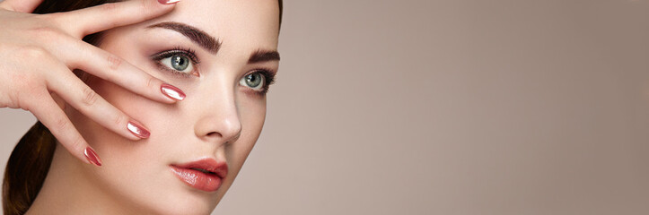 Beauty brunette woman with perfect makeup. Red lips and nails. Perfect eyebrows. Skin care foundation. Beauty girls face isolated on beige background. Fashion photo