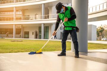 A man Janitor  wear face mask cleaning Floor With Mopping  on modern building