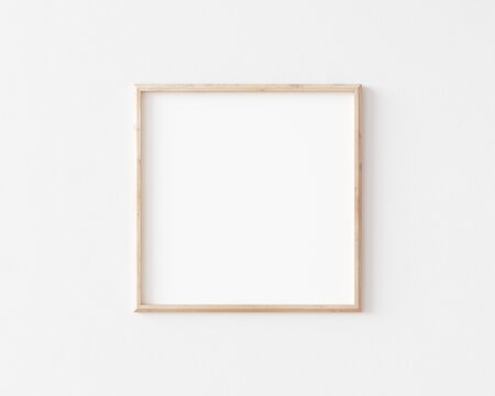 Thin square wooden frame on white wall. 3d illustration.