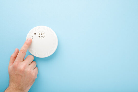 Young man finger touching new white plastic smoke alarm. Light blue table background. Pastel color. Safety concept. Empty place for text.