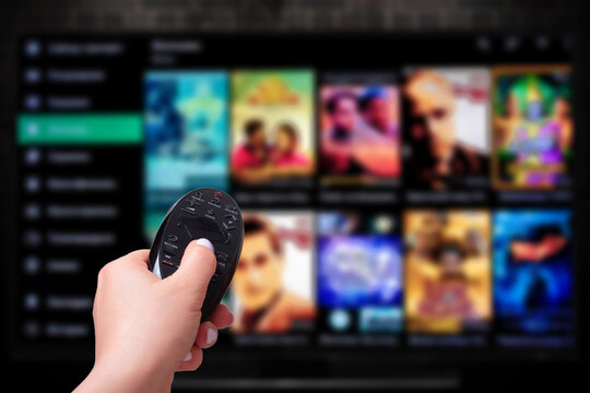Multimedia streaming concept. Hand holding remote control. TV screen with lot of pictures.