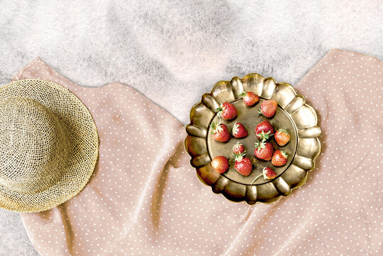 Retro dusty pink dress, straw hat and strawberry in vintage brass dish.
