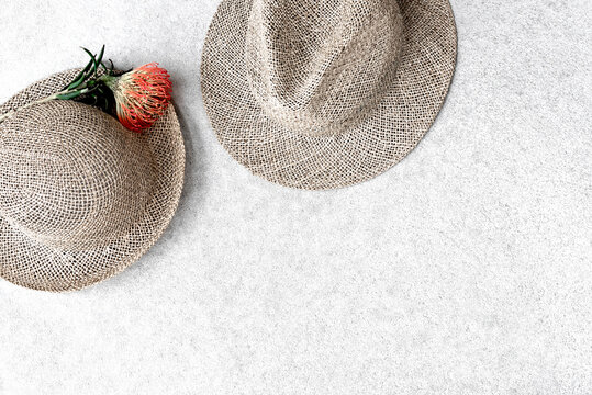 Straw hats for woman and man on concrete background.