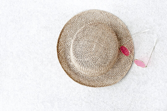 Straw hats for woman and pink sunglasses on concrete background.