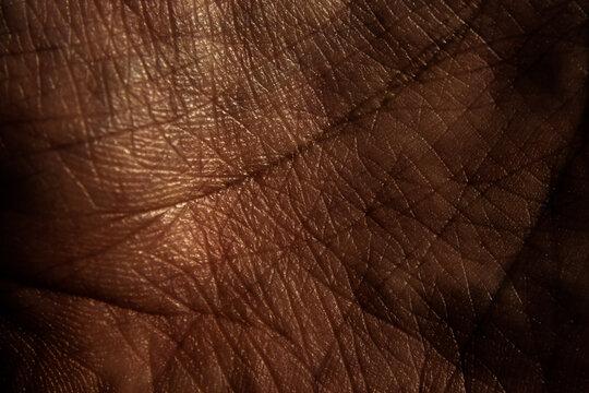 Black human palm skin texture background