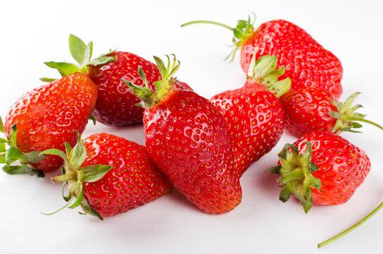 Ripe juicy strawberies on the white background.Group f fresh summer fruit