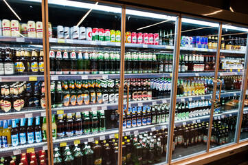 Kyiv, Ukraine - December 19, 2018: Different beer bottles on shelves of fridge in a supermarket.