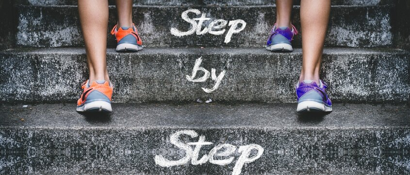 People climbing the stairs with [Step by Step] written on them - concept of success