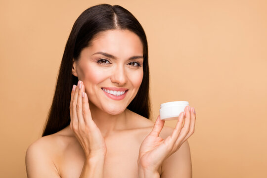 Closeup photo of mature nude lady toothy model natural beauty no makeup holding anti age cream bottle applying touch soft cheek isolated beige pastel color background