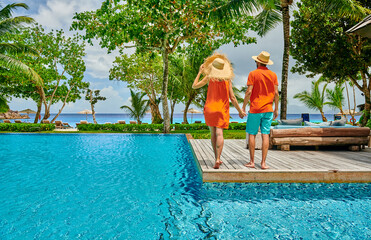 Fototapete - Young couple by poolside. Resort swimming pool at Seychelles.