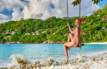 Fototapete - Woman swinging at tropical beach, Seychelles.