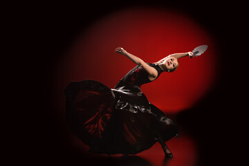 young flamenco dancer in dress holding fan while dancing on red and black
