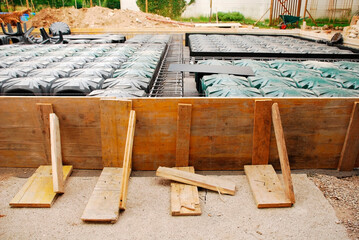 A house foundation site with steel reinforcement cages and radon iglus surrounded by wooden shuttering. The cages and iglus have been laid out ready for the concrete to be poured.