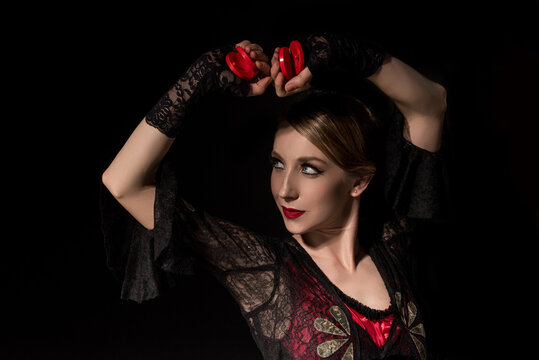 attractive dancer holding castanets while dancing flamenco isolated on black