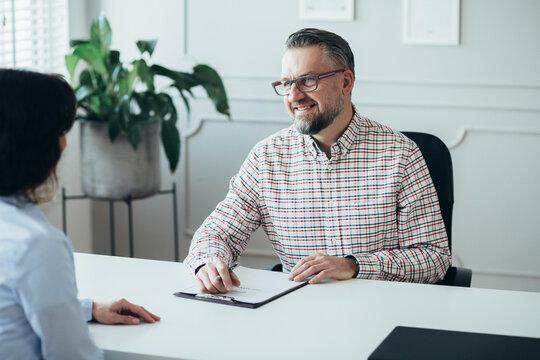 Handsome senior boss interviewing an elegant business woman