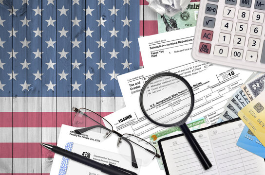 IRS form 1040NR Nonresident Alien Income tax return lies on flat lay office table and ready to fill. U.S. Internal revenue services paperwork concept. Time to pay taxes in United States