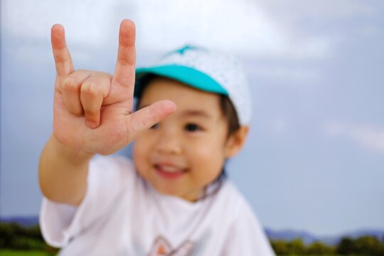 "An adorable little asian girl show her hand, the sign hand language ""I love you"". Blured of her face, focus at her finger."