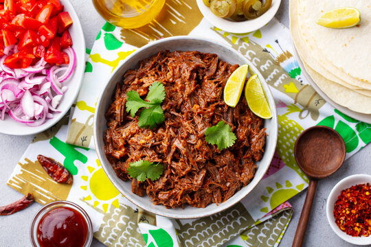 Mexican shredded beef with tortillas, vegetables and sauce. Grey background. Top view.