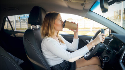 Beautiful blonde woman drinking coffee in car while commuting to work