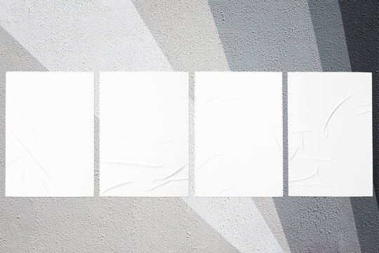 Closeup of geometrical gray painted urban wall texture with four wrinkled glued poster templates. Modern mockup for design presentation with clipping path. Creative urban city background.