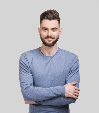 Portrait of handsome smiling young man with folded arms. Serious cheerful men with crossed hands studio shot. Isolated on gray background