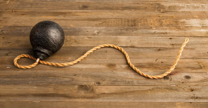 classic round black antique bomb with a long non-burning rope wick on a rough wooden background
