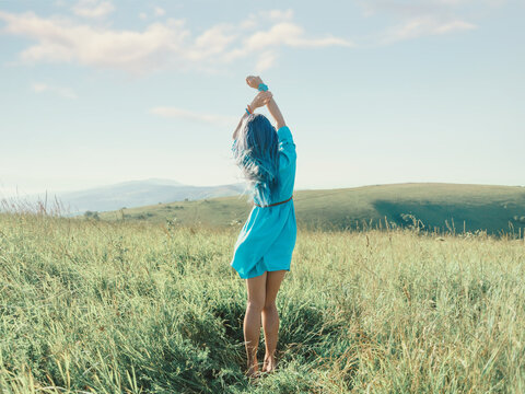 Romantic blue hair woman standing with hands up in summer meadow.