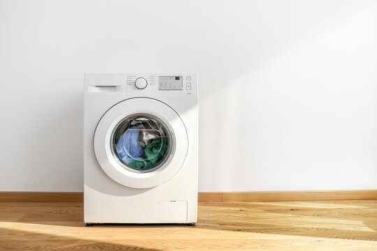 Working washing machine on white background