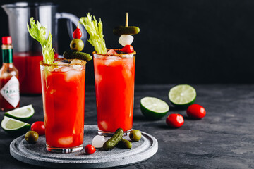 Bloody Mary Cocktail in glasses with garnishes. Tomato Bloody Mary ice cold drink with fresh celery, pickles and lime
