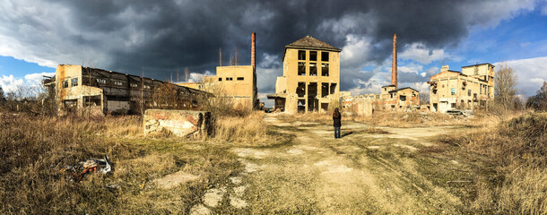 Abandoned ruined factory in sun with dark clouds
