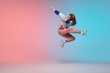 Printed kitchen splashbacks Dance School In jump. Beautiful girl dancing hip-hop in stylish clothes on colorful gradient background at dance hall in neon light. Youth culture, movement, style and fashion, action. Fashionable bright portrait.
