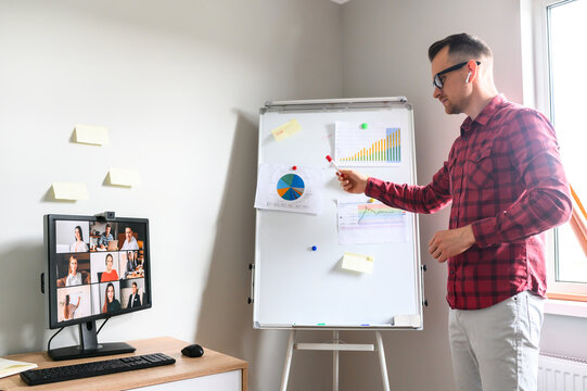 Young employee in glasses provides a statistical report to a board of directors via online video call, he shows statistical data on a flipchart
